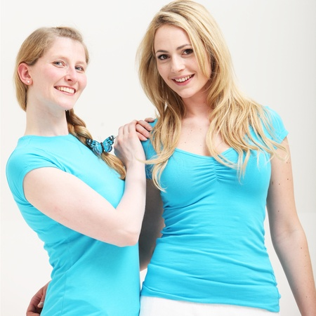 busty woman: Two smiling young blonde women standing close together.