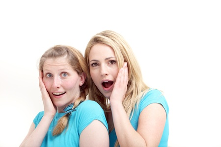 reacting: Two wide eyed female friends reacting in astonishment and incredulity as they stand close together with their hands to their cheeks