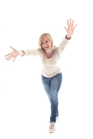 Beautiful vivacious blonde woman laughing as she leans forwards reaching towards the camera with both hands outstretched photo