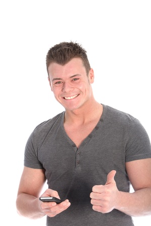 Smiling handsome young man holding a mobile phone in one hand giving a thumbs up of approval and success at news he has just received isolated on white photo