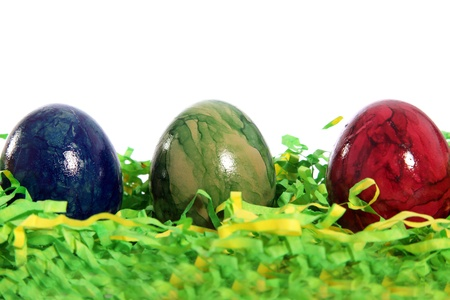 Three marble patterned Easter Eggs in blue, green and red nestled in a bed of green artificial straw against a white background photo