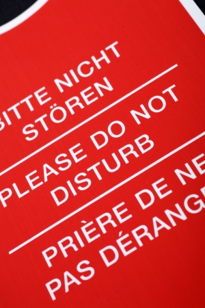 Do not disturb   sign written in different languages, close up photo