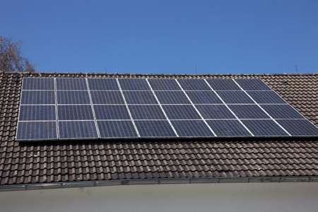 photoelectric: An array of photovoltaic solar panels mounted on a house roof to supply renewable domestic electricity by converting the radiant energy of the sun