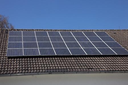 radiacion solar: Una serie de paneles solares fotovoltaicos montados sobre un tejado de la casa para el suministro nacional de electricidad renovable mediante la conversión de la energía radiante del sol