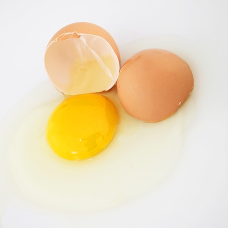 albumin: Cracked fresh hens egg with the bright yellow yolk and transparent albumin or egg white running over a white background