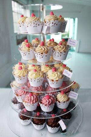 Elegant delicious cupcakes exposed in a confectionery shop, closeup photo