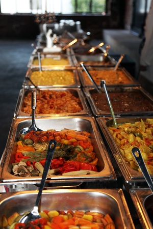 heated: Long row of hot vegetables in stainless steel containers on a catered buffet at a wedding reception or function