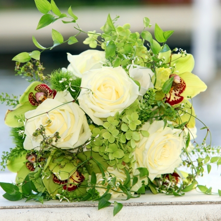floral arrangements: Closeup of a beautiful bouquet of cream coloured roses and green orchids with delicate foliage lying on a white surface Stock Photo