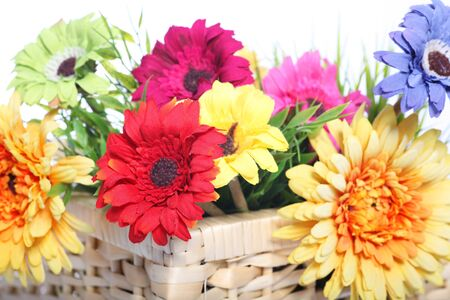 Bright colourful arrangement with a selection of different summer flowers in a basket, closeup on a white background photo