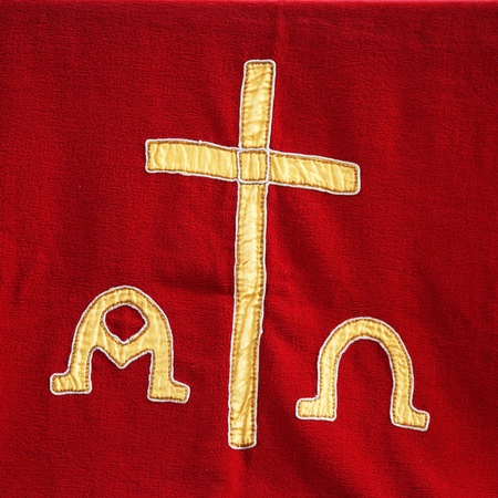vestment: Decorative symbolic gold needlework on a priests vestment or church cloth with a gold cross and religious icons on a red background