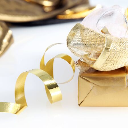 seasonal greeting: Closeup of a pretty gold wrapped gift and twirled ribbon on a white background for your seasonal greeting