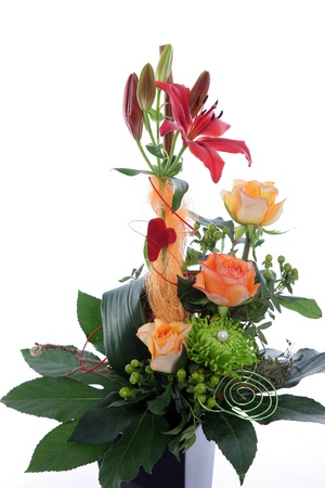 Formal floral wedding arrangement with colourful flowers including roses and tiger lilies with a base of greenery and a red heart photo