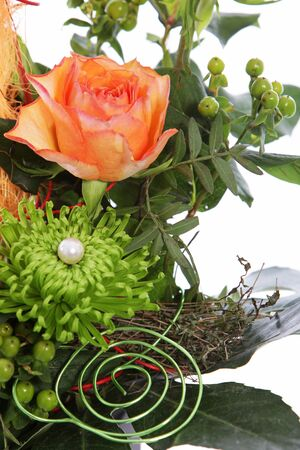 Flowers in a creative wedding display with spiral wires and a pearl on greenery with an orange rose photo