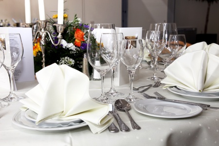 Stylish white table setting with elegant glassware, silverware and a floral centrepiece at a wedding reception photo