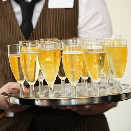 alcoholic man: Closeup view of the hands of a waiter carrying a tray of champagne in tall elegant flutes at a wedding reception or catered event
