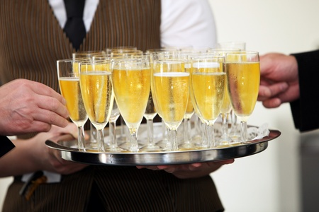 function: Tray of chilled champagne in elegant flutes being carried by a waiter at a catered event with male hands helping themselves to a glass Stock Photo