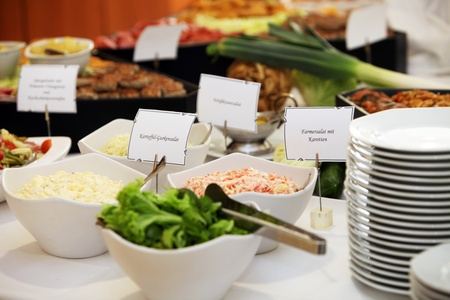 identifying: Fresh vegetable salads in dishes on a buffet table with name labels identifying ingredients