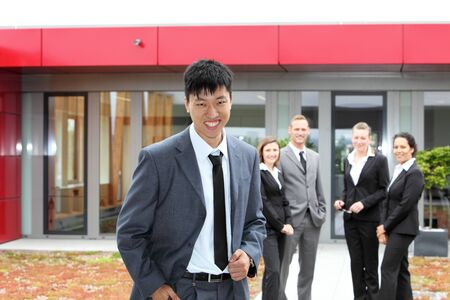 Smiling Chinese businessman with his colleagues at his back photo