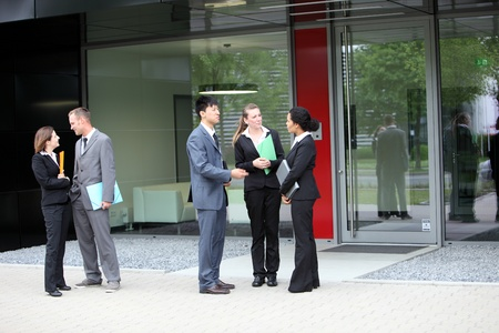 A group of businesspersons talking with two business couple on the side photo