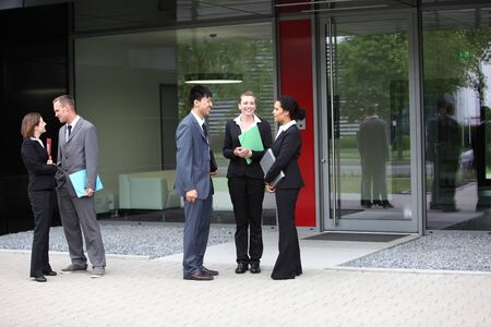 Business colleagues talking with two business couple on the side photo
