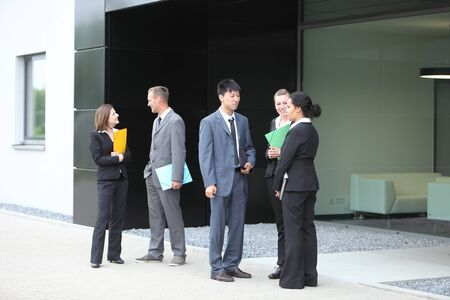 A group of Professional businesspeople talking in the lobby of office building photo