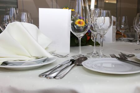 Luxury place setting with a menu card, elegant glassware and linens at a catered function or celebration photo