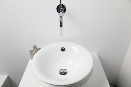 handbasin: Closeup view of a modern circular ceramic handbasin and wall mounted tap in a bathroom