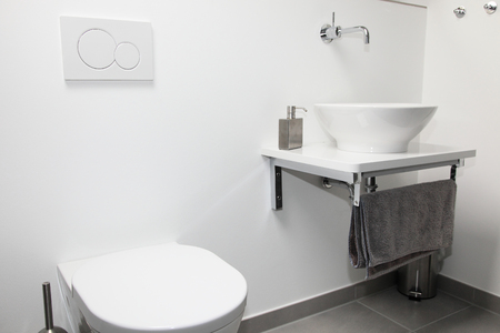 tap room: Modern bathroom interior with a wall mounted tap and ceramic hand basin and toilet