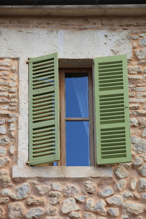 quaint: Window with green wooden shutters half open in a stone building with walls made of natural rocks Stock Photo