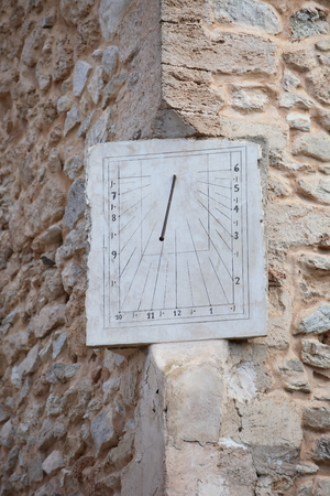 corner clock: Old rectangular metal clock or sundial with hour graduations set into the corner of an old stone building Stock Photo