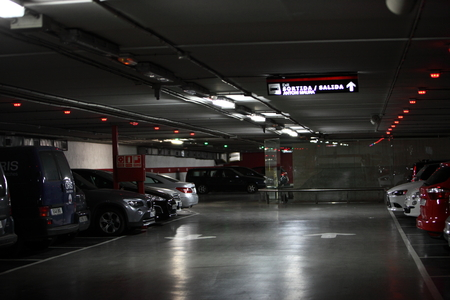 Deserted interior of a covered vehicle parking lot with a variety of different parked cars illuminated at night
