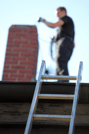 chimneys: Chimney sweep at work on a roof with a ladder balanced against the guttering and focus to the ladder