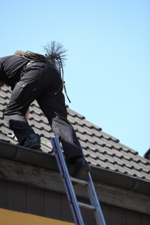 Chimney sweep climbing onto the roof of a house with his wire brush , rope and tools strapped to his back photo