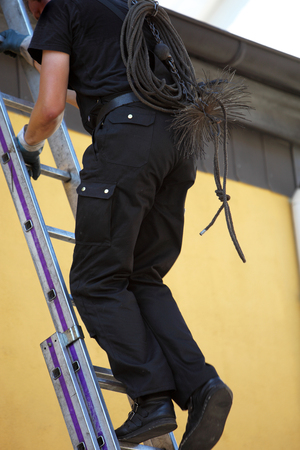 flue: Chimney sweep climbing up to the roof of a house with his equipment over his back as he prepares to clean out the chimney flue