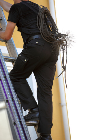 chimneys: Chimney sweep climbing a stepladder with his equipment and wire brush slung over his back