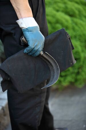 chimney sweep: Chimney sweep holding a curved metal scraping tool for dislodging soot and debris from inside a chimney flue Stock Photo