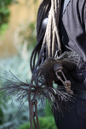 Coarse wire brushes and euipment of a chimney sweep slung over the back of a workman, close up view photo