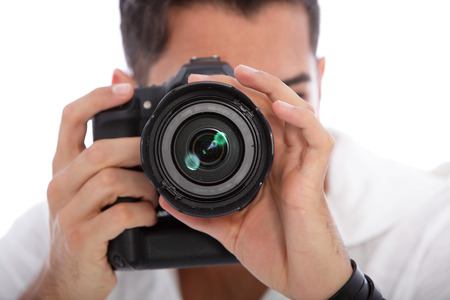 focus shot: Male photographer taking a photograph focusing directly at the lens with his professional dslr camera
