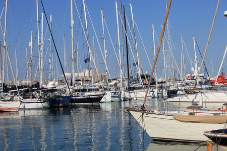 sheltered: Pleasure boats and yachts moored in the sheltered water of a marina under a sunny blue summer sky