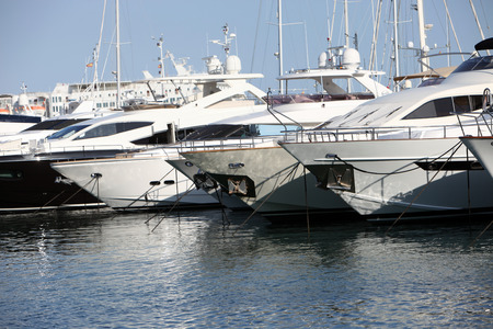 sheltered: Row of luxury motorised yachts moored in a sheltered harbour, close up view of the bows Stock Photo