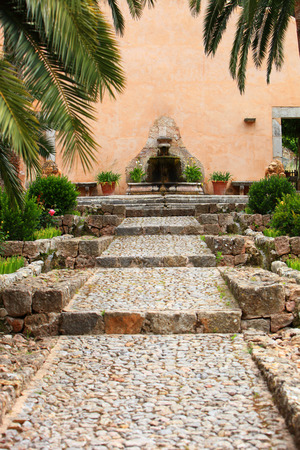 palm lined: Cobbled walkway leading between tropical palm trees to a garden fountain in a high wall