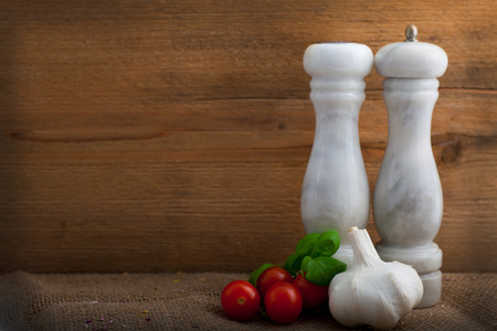 pepper grinder: Condiments, herbs and flavouring for the cook with a rustic still life arrangement of salt and pepper mills, fresh basil, garlic, and ripe red tomatoes against a wooden panel with copyspace