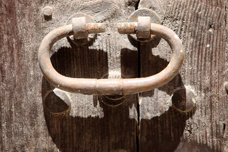 bolted: Old rusty door knocker or handle in a simple oval shape mounted on a rustic wooden door, close up view