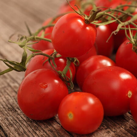 vine country: Close up of whole uncooked fresh ripe red cherry tomatoes still attached to the vine lying on a rough wooden surface Stock Photo