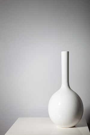 minimalist interior: Elegant white vase on a small table against a white wall with copyspace and vignette