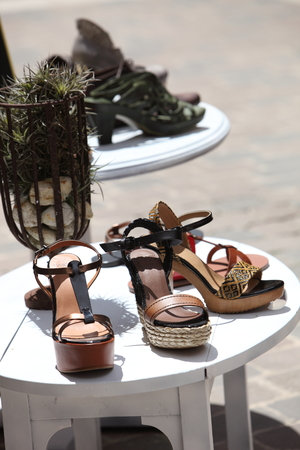 enticement: Displayed For Sale Wedge Sandals on White Wooden Table Outdoor.