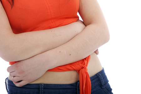 constipation symptom: Close up White Woman in Orange Shirt Crossing her Arm at her Stomach. Isolated on White Background. Stock Photo
