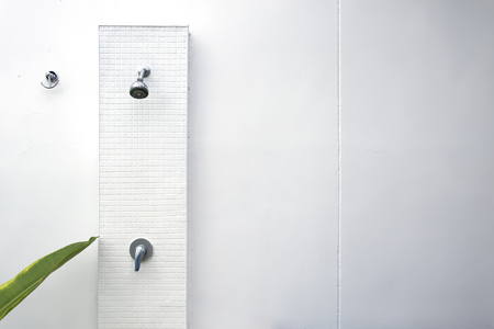 luxury room: Wall shower on white wall background before swimming in swimming pool.
