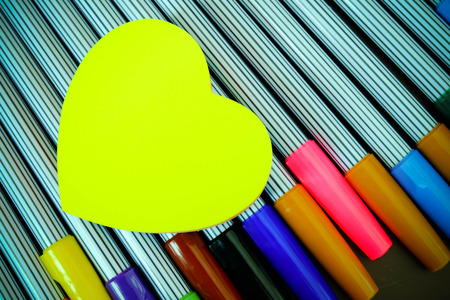 Yellow heart paper on color pens photo
