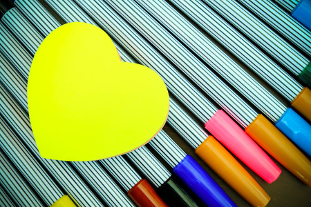 Yellow heart shape paper on color pens photo
